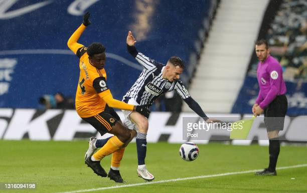 Conor Townsend of West Bromwich Albion is challenged by Owen Otasowie of Wolverhampton Wanderers during the Premier League match between West...