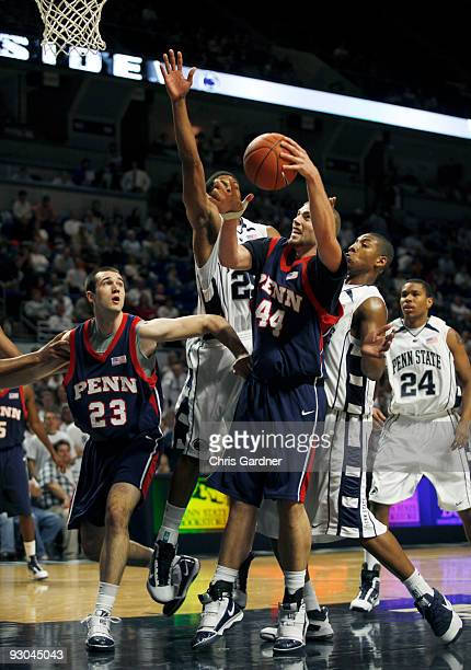 Conor Turley of the Penn Quakers drives to the basket while being covered by Andrew Jones of the Penn State Nittany Lions as Mike Howlett of the Penn...