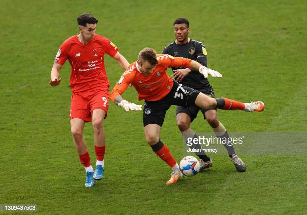 Conor Wilkinson of Leyton Orient clashes with goalkeeper Laurie Walker of Oldham and Kyle Jameson of Oldham during the Sky Bet League Two match...