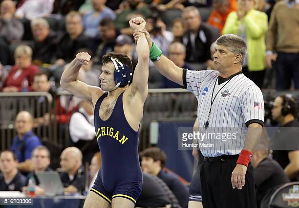 Conor Youtsey of the Michigan Wolverines gets his hand raised after his upset victory over Eddie Klimara of the Oklahoma State Cowboys during the...