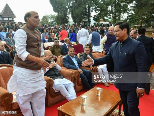 Conrad Sangma president of the National Peoples Party and backed by the Bharatiya Janata Party shakes hands with Indian Home Minister Rajnath Singh...