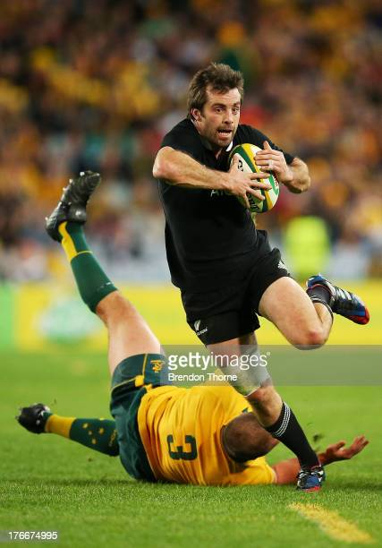 Conrad Smith of the All Blacks breaks the tackle of Ben Alexander of the Wallabies during The Rugby Championship Bledisloe Cup match between the...
