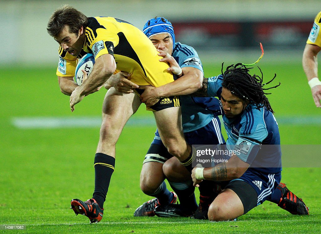 Conrad Smith of the Hurricanes is tackled by Benson Stanley and Ma'a Nonu (R) of the Blues during the round 11 Super Rugby match between the Hurricanes and the Blues at Westpac Stadium on May 4, 2012 in Wellington, New Zealand.