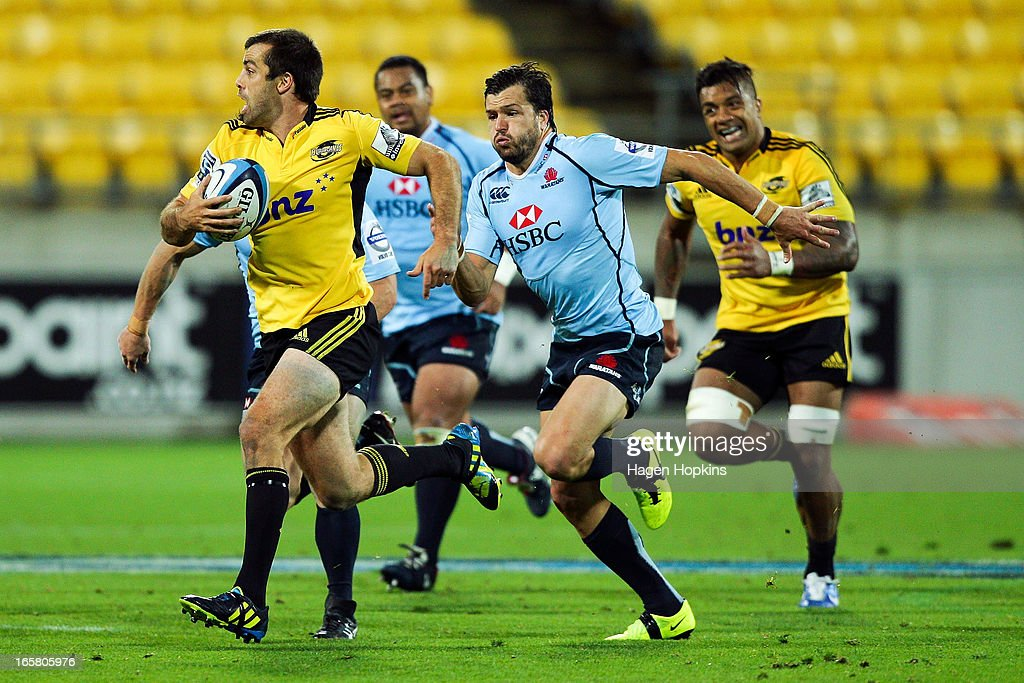 Conrad Smith of the Hurricanes makes a break while Adam Ashley-Cooper of the Waratahs chases during the round eight Super Rugby match between the Hurricanes and the Waratahs at Westpac Stadium on April 6, 2013 in Wellington, New Zealand.