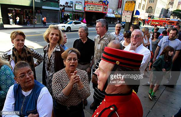 LA Conservancy volunteer Rory Cunningham wears a 1930s theater usher's uniform as he works the crowd outside th Palace Theatre on Broadway on Sunday...