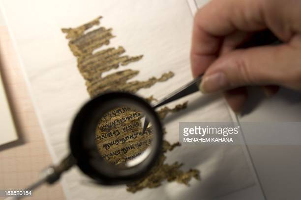 A conservation analyst from the Israeli Antiquities department examines fragments of the 2000yearold Dead Sea scrolls at a laboratory in Jerusalem...
