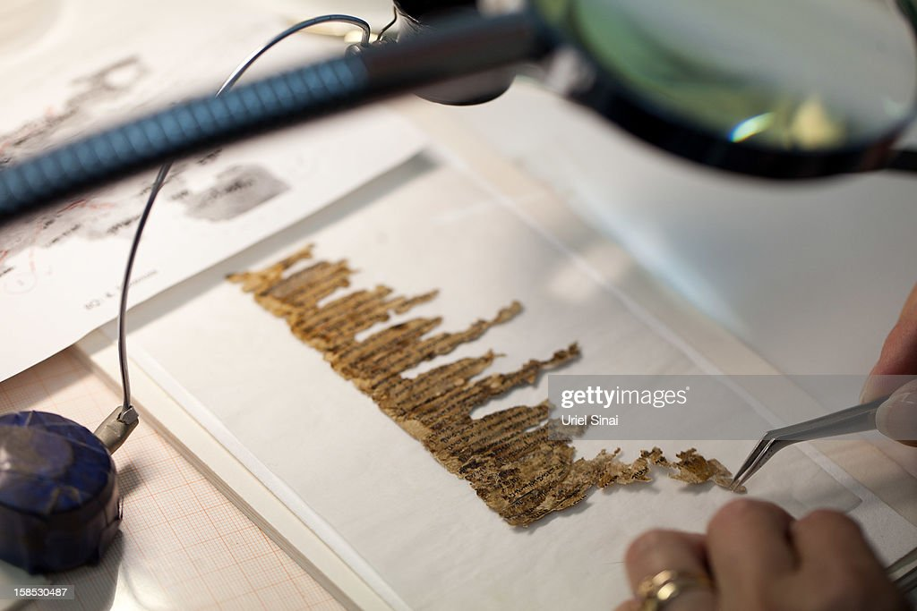 A conservation analyst from the Israeli Antiquities department examines fragments of the 2000-year-old Dead Sea scrolls at a laboratory before photographing them on December 18, 2012 in Jerusalem, Israel. More than sixty years after their discovery Israel have put 5,000 fragments of the ancient Dead Sea scrolls online in a partnership with Google.
