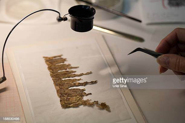A conservation analyst from the Israeli Antiquities department examines fragments of the 2000yearold Dead Sea scrolls at a laboratory before...