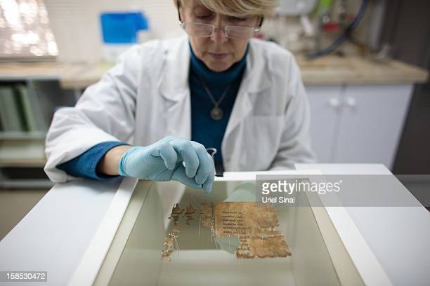 A conservation analyst from the Israeli Antiquities department prepares fragments of the 2000yearold Dead Sea scrolls at a laboratory before...