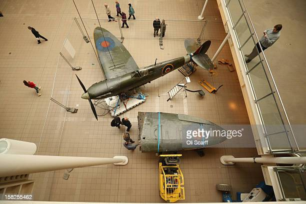 Conservation Officers remove a wing from a Mk I Spitfire that had been suspended from the ceiling in the Imperial War Museum on December 12 2012 in...