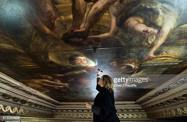 Conservationist Sarah Pinchin inspects her teams work on Rubens ceiling painting 'Wise rule of James 1st' and shines a light on an image of James 1st...