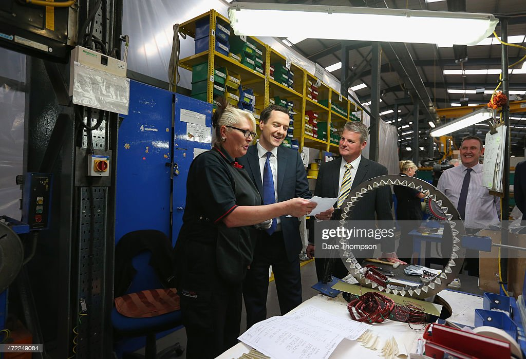Conservative Chancellor George Osborne with supervisor Jane Paley as he works on part of a generator during a visit to Winder Power on May 5, 2015 in Pudsey, England. The British public go to the polls in the general election on May 7th.