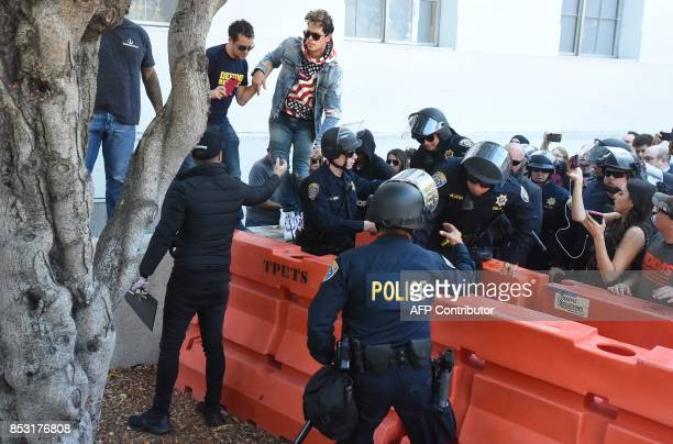Conservative commentator Milo Yiannopoulos climbs over a barrier as he is escorted out of the University of California Berkeley campus where he spoke...