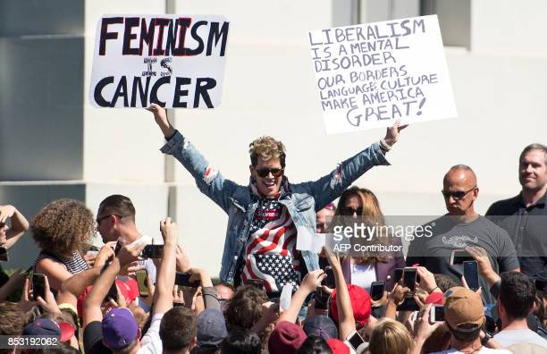 Conservative commentator Milo Yiannopoulos holds up signs to a crowd of supporters on the University of California Berkeley campus on September 24...