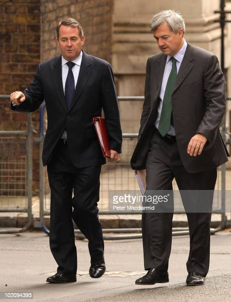 Conservative Defence Secretary Dr Liam Fox walks with Liberal Democrat Energy and Climate Change Secretary Chris Huhne as they arrive for the weekly...