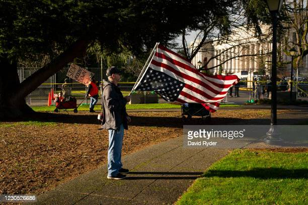 Conservative demonstrator holds a U.S. Flag upside down as an anti-vaccination demonstrator walks nearby at the Washington State Capitol campus on...