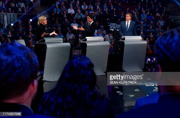 Conservative leader Andrew Scheer looks on as Green Party leader Elizabeth May and Canadian Prime Minister and Liberal leader Justin Trudeau discuss...