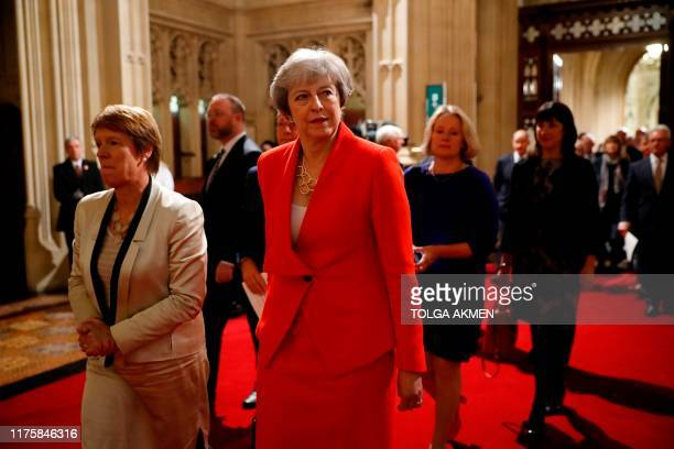 Conservative MP and former prime minister Theresa May processes with members of parliament through the Peers Lobby into the House of Lords to listen...