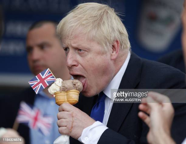 TOPSHOT Conservative MP and leadership contender Boris Johnson tastes an ice cream as he campaigns in Barry Island west of Cardiff in south Wales on...