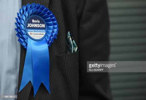 A Conservative Party activist wears a rosette as they wait for the results in the count centre in Uxbridge where Britain's Prime Minister and...
