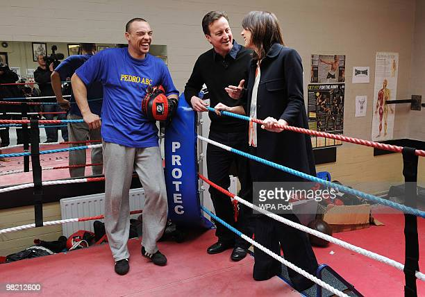 Conservative Party Leader David Cameron and his wife Samantha Cameron speak with boxing instructor Simon Lewin during a visit to the Pedro Club in...