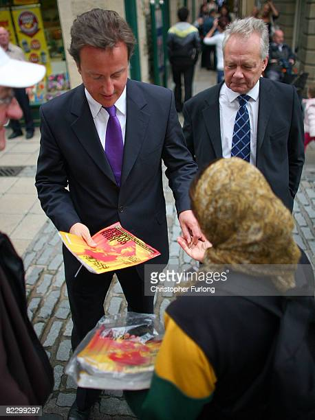 Conservative Party leader David Cameron and prospective candidate Eric Ollerenshaw buy a Big Issue during a tour of Lancaster England on August 14...