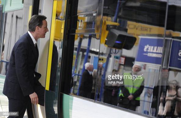 Conservative party leader David Cameron boards a train on ...