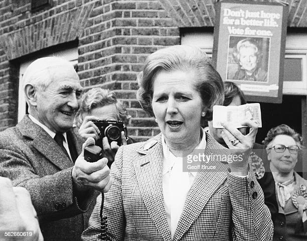 Conservative Party leader Margaret Thatcher holding up a one pound note to the press to illustrate the devaluation and inflation of the note as she...