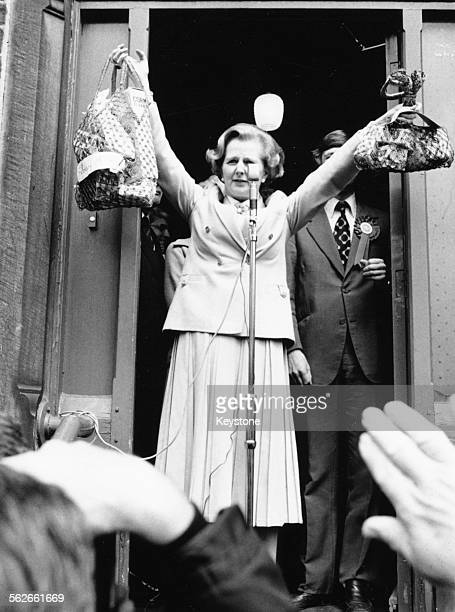 Conservative Party leader Margaret Thatcher holding up two different sized shopping bags, illustrating the difference between the drop in the value...