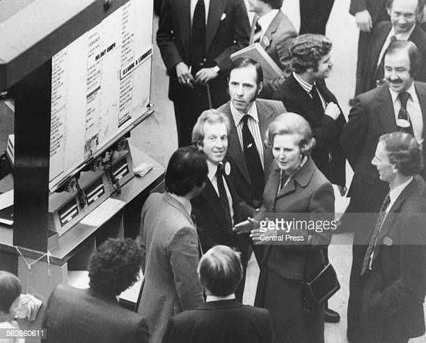 Conservative Party leader Margaret Thatcher talking to men on the floor of the Stock Exchange, as trading gets in to full swing on the Ladbrokes,...