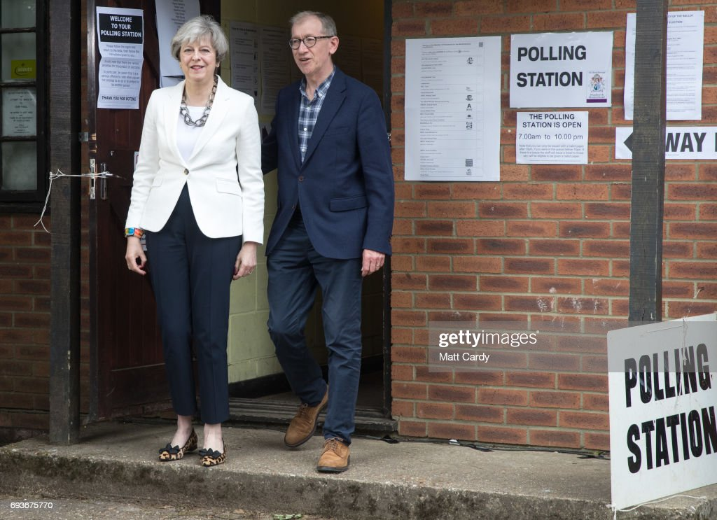 Conservative Party leader Theresa May and husband Philip leave the polling station in Sonning Guide & Scout hut after casting their vote on June 8, 2017 in Sonning near Maidenhead, England. Polling stations have opened as the nation votes to decide the next UK government in a general election.