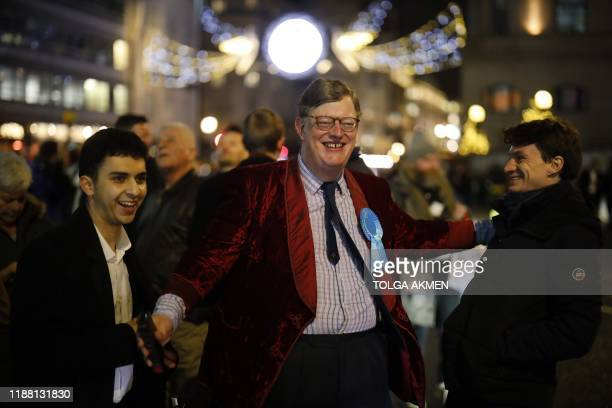 Conservative Party supporter reacts after the broadcaster's exit poll results shows Britain's Prime Minister Boris Johnson's Conservative Party being...