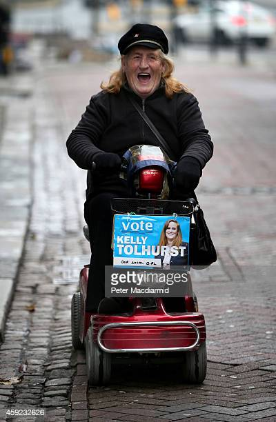 Conservative party supporter rides a mobility scooter decorated with a poster of candidate Kelly Tolhurst on November 19 2014 in Rochester England A...
