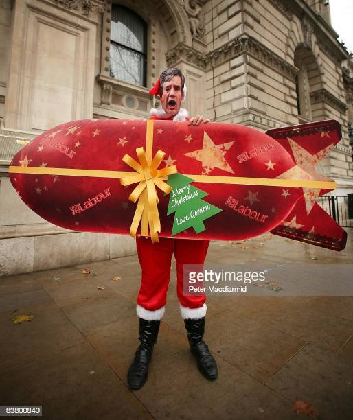 Conservative Party supporter wearing a mask depicting Prime Minister Gordon Brown carries a representation of a Labour party 'tax bombshell' near...