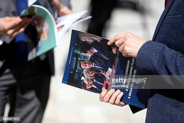 Conservative Party supporters hold copies of their party's manifesto after David Cameron UK prime minister and leader of the Conservative Party...