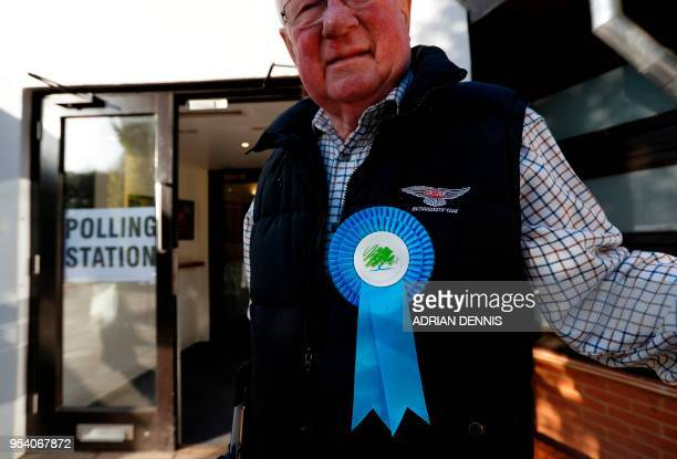 Conservative Party teller waits for voters to arrive at a polling station in Hartley Wintney, Hampshire, some 45 miles west of London on May 3, 2018....