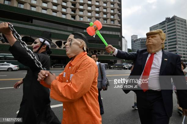 A conservative proUS activist wearing a mask of US president Donald Trump stages a performance with a colleague wearing a mask of North Korean leader...
