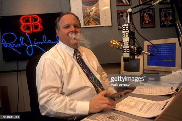 Conservative radio talk show host Rush Limbaugh takes a break and smokes a cigar during his radio show