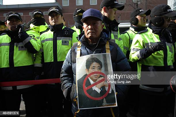 Conservative South Korean man holds a portrait of Japanese Prime Minister Shinzo Abe during a demonstration as South Korea marks the forthcoming 96th...