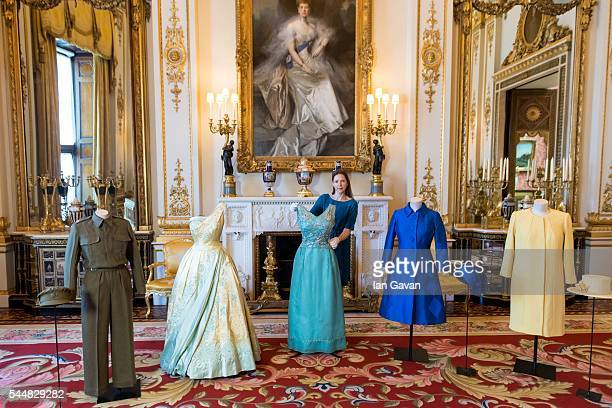 A conservator attends to outfits from the Queen's wardrobe during the press preview of 'Fashioning A Reign 90 years Of Style From The Queen's...