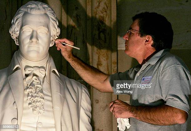 Conservator Cameron Wilson of New York City cleans up the ear of a sculpture of founding father and the first Secretary of the Treasury Alexander...