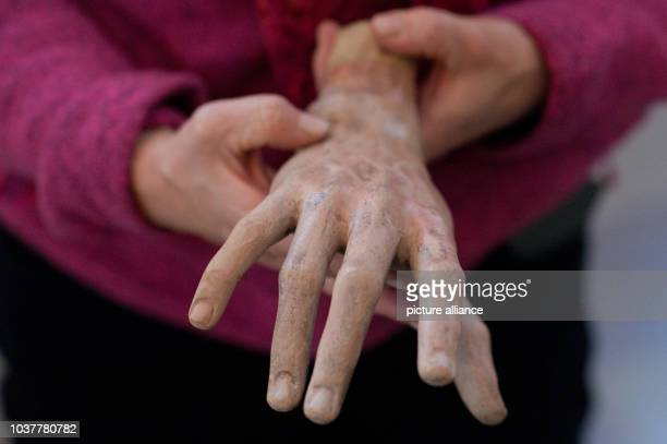 Conservator Dorothee SchmidtBreitung holds up the restored hand of the sculpture of John at the Church of the Holy Cross inNeuzelle Germany 01...