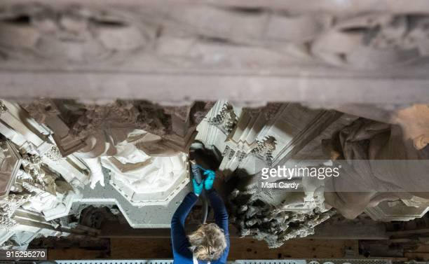 A conservator from McNeilage Conservation uses a soft brush and vacuum cleaner to clean accumulated dust and dirt from part of the intricate stone...