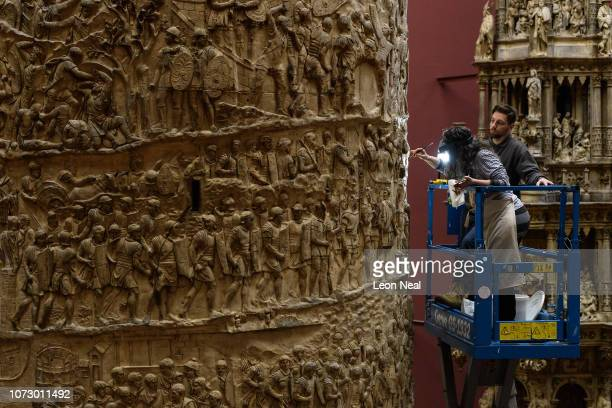 """Conservator works on one half of a cast of the Roman """"Trajan's Column"""" memorial at a press preview of the Cast Courts at The V&A on November 27, 2018..."""