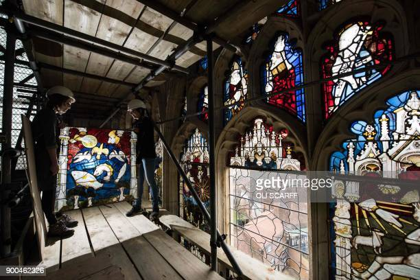Conservators Zoe Harrigan and Anna Milsom replace the final stained glass panel in York Minster's 600 year-old Great East Window, following a 10-year...