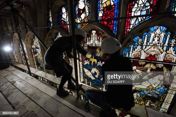 Conservators Zoe Harrigan and Anna Milsom replace the final stained glass panel in York Minster's 600 yearold Great East Window following a 10year...