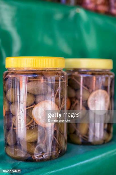 Conserved capers in glass jars for sale in the village market.