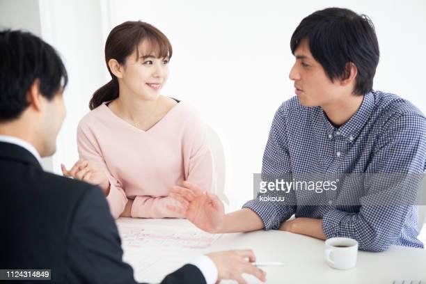 カップルで幸せな相談をしながら新居をご検討ください。 - 妻 ストックフォトと画像