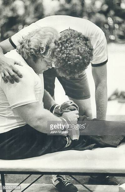 Consolation American coach Phil Boucher kneels over weightlifter Jon Brown yesterday after US champ failed to lift past 529 pounds still good enough...