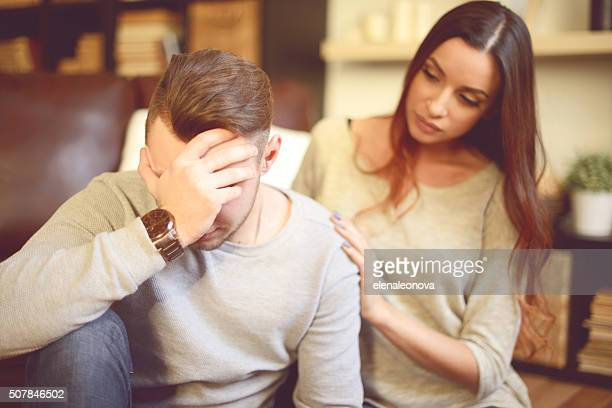 consoling her depressed boyfriend - heterosexual couple stock pictures, royalty-free photos & images